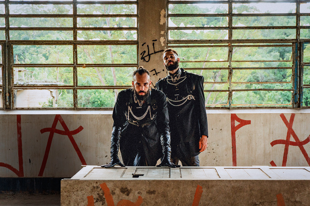 gêmeos 2DE1 posando para clipe gravado em sala pixada