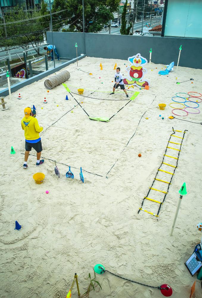 A imagem mostra Lalau com outra criança em uma quadra de areia. Há uma rede entre eles, vários objetos de treinos espalhados fora da quadra e a criança está em posição de expectativa com sua raquete