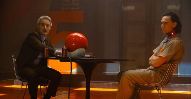 Sentados em uma mesa, Owen Wilson e Tom Hiddleston em cena de Loki