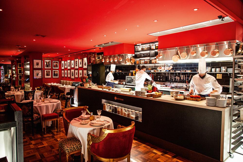 Restaurante com paredes vermelhas, balcão de bar e mesas