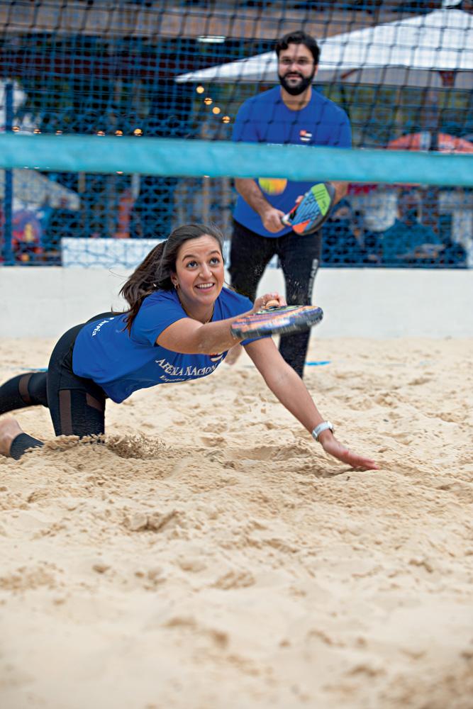 A imagem mostra Jessica pulando no chão de areia para tentar buscar uma bola com a raquete