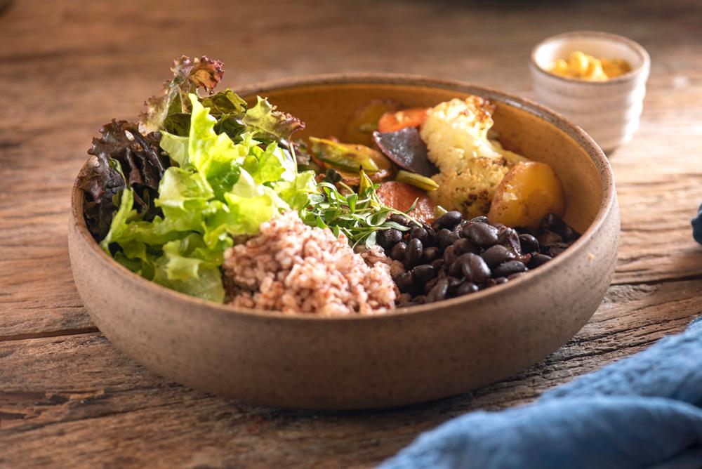 Cumbuca de cerâmica sobre mesa de madeira com arroz, feijão-carioquinha, vegetais salteados e salada verde mais farofa de castanhas.