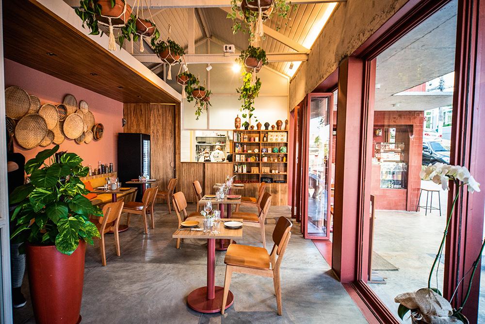 Salão do restaurante Camélia Òdòdó , com paredes pintadas em tons terrosos, aberto para a rua do lado esquerdo.