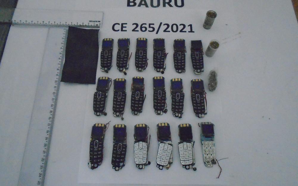 A imagem mostra 18 celulares deformados em cima de uma mesa branca com réguas ao lado