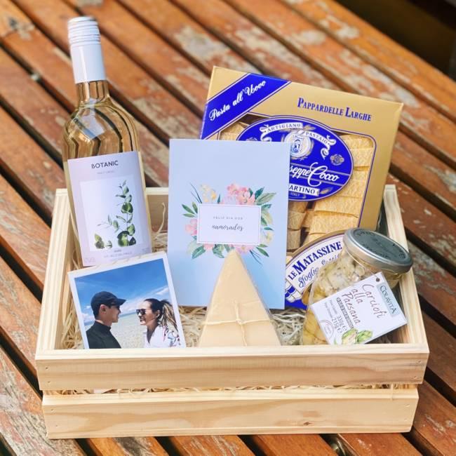 Em uma cesta de madeira, itens como polaroid com foto de casal, vinho, cartão, queijo, alcachofras e massa italiana. Itens tem tom azul