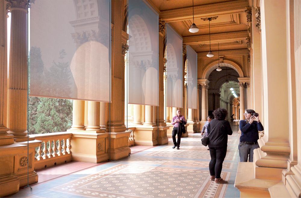 A imagem mostra um corredor do Museu do Ipiranga, na área externa, com as telas cobrindo a entrada do sol no corredor.