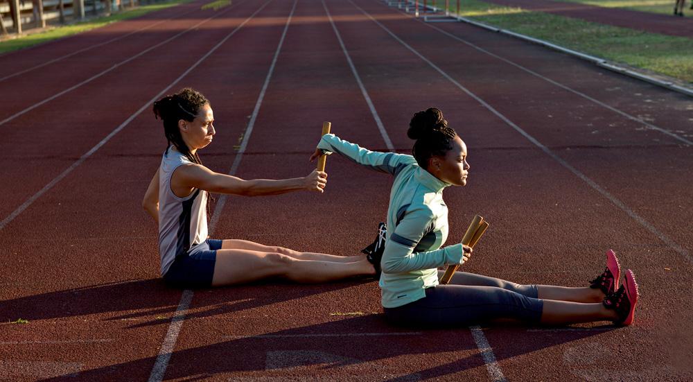A imagem mostra duas atletas no longa sentadas numa pista, praticando a troca de bastão