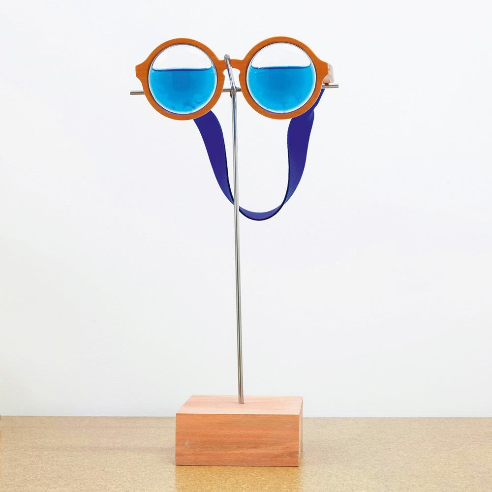 Foto mostra uma obra em cima de uma mesa, que é um óculos com água nas lentes