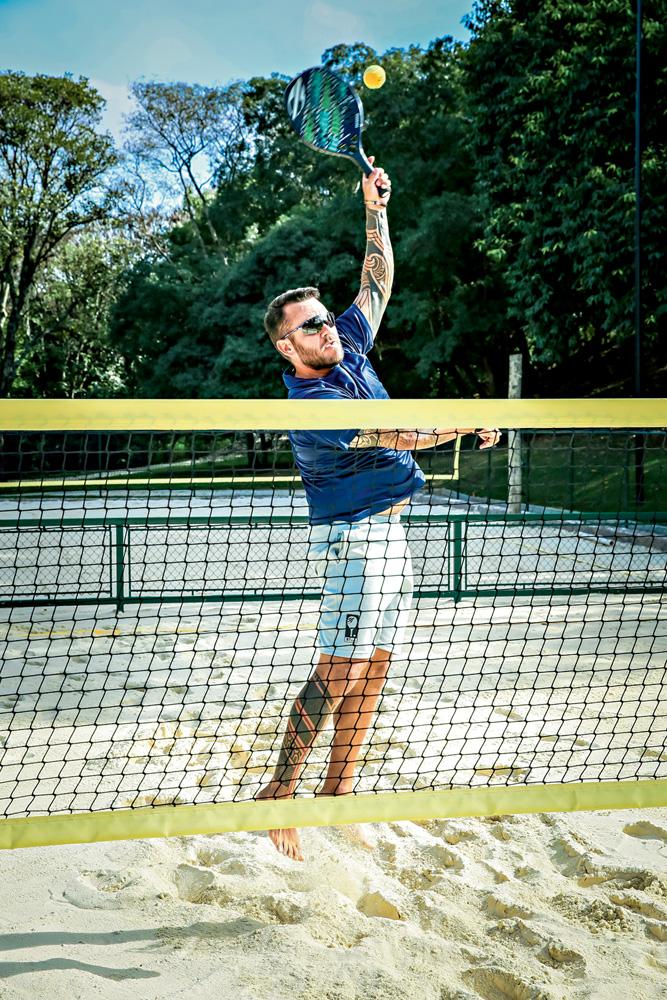 A imagem mostra o professor se esticando para acerta a bolinha do beach tennis no alto. Ele está em uma quadra de areia.