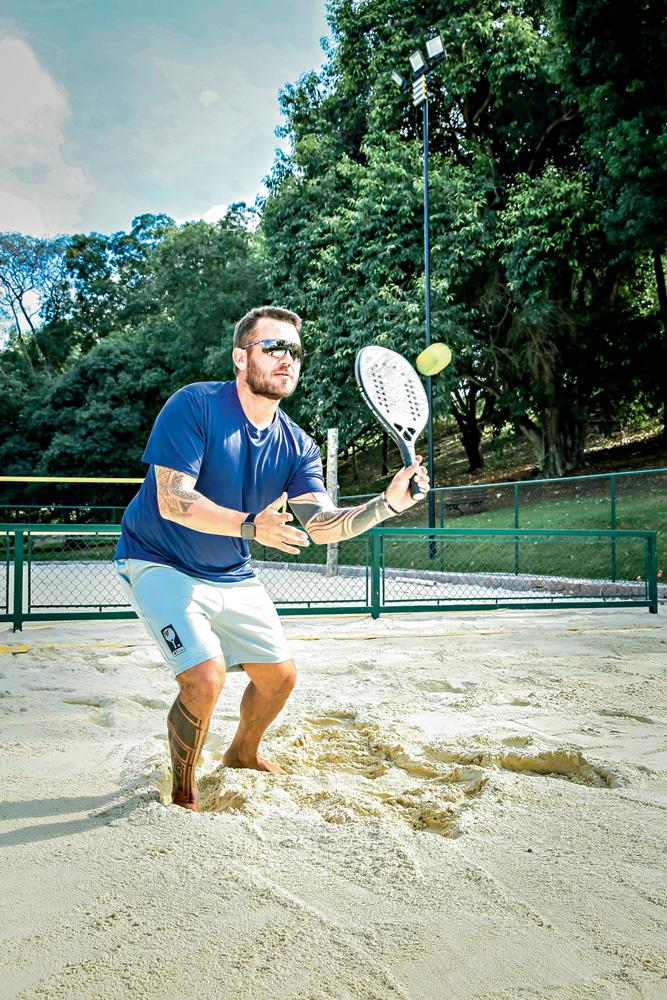 A imagem mostra o professor acertando a bolinha em uma altura média. Ele está em uma quadra de beach tennis, com os joelhos flexionados para acertar a bola na altura do seu ombro.