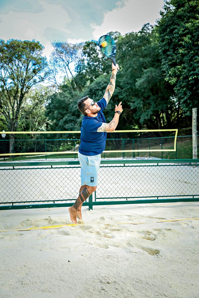 A imagem mostra o professor acertando a bola de beach tennis em uma quadra de areia.