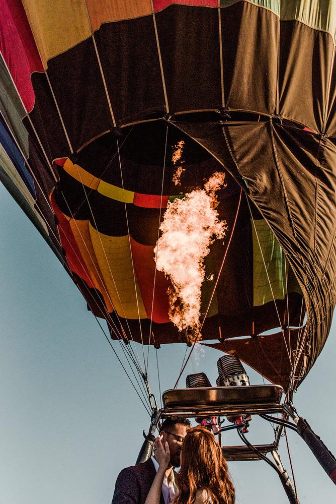 Foto mostra um balão nas alturas, com chamas para seu funcionamento. Nele, um casal se beija