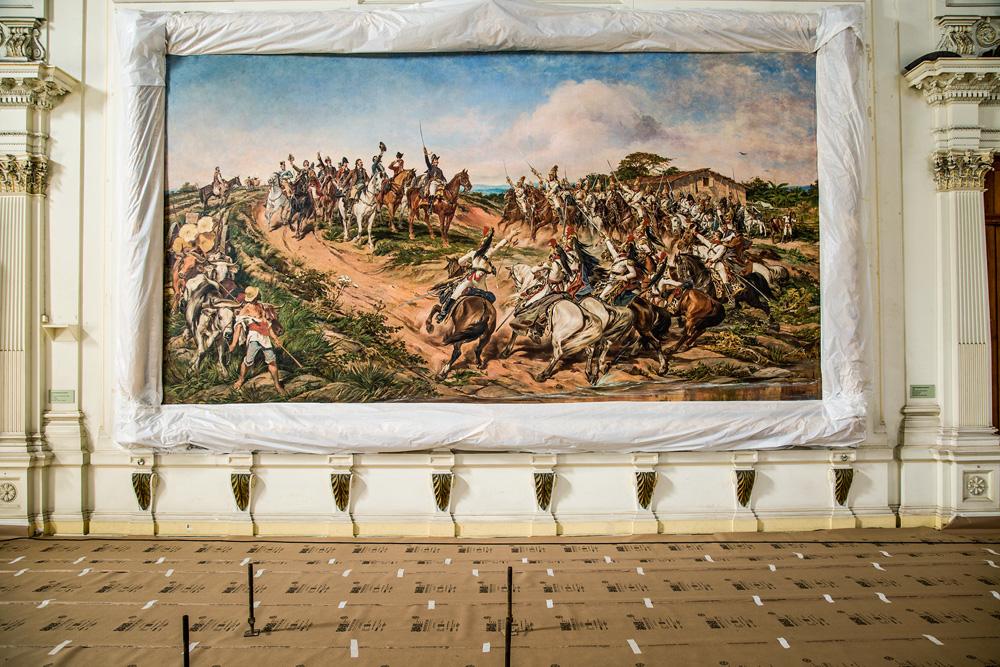 A imagem mostra o quadro de Pedro Américo após a restauração, na parede do Museu do Ipiranga.