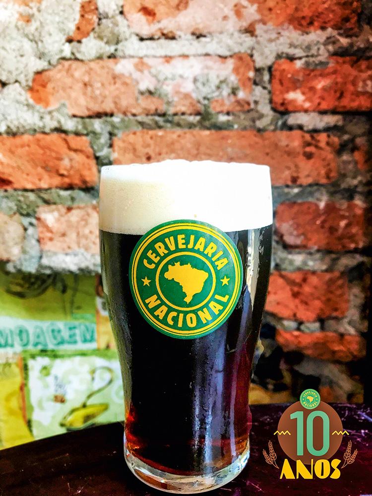 Copo de chope com símbolo da Cervejaria Nacional completo com cerveja de coloração escura com colarinho.