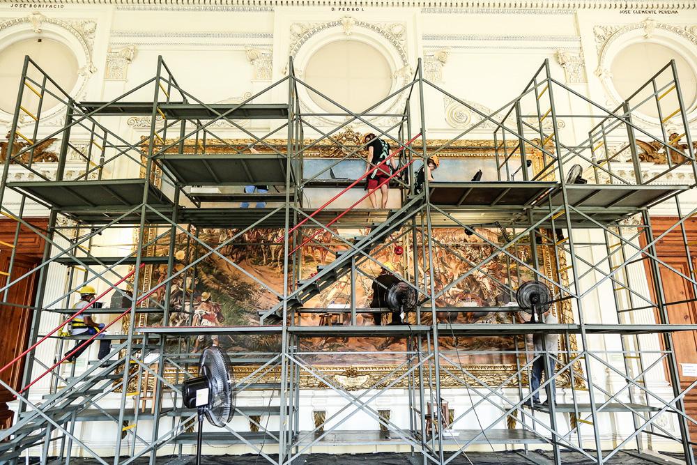 A imagem mostra um andaime montado em frente ao quadro de Pedro Américo. Nele, há profissionais de capacete e máscara observando de maneira bem próxima o quadro.