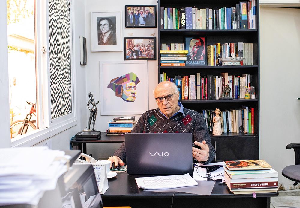 eduardo suplicy sentado em seu escritório na frente de seu notebook e olhando para a foto