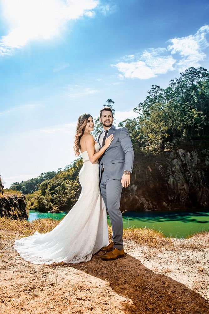 karine e guilherme posando para a foto com vestes de casamento com vista bonita da pedreira ao fundo