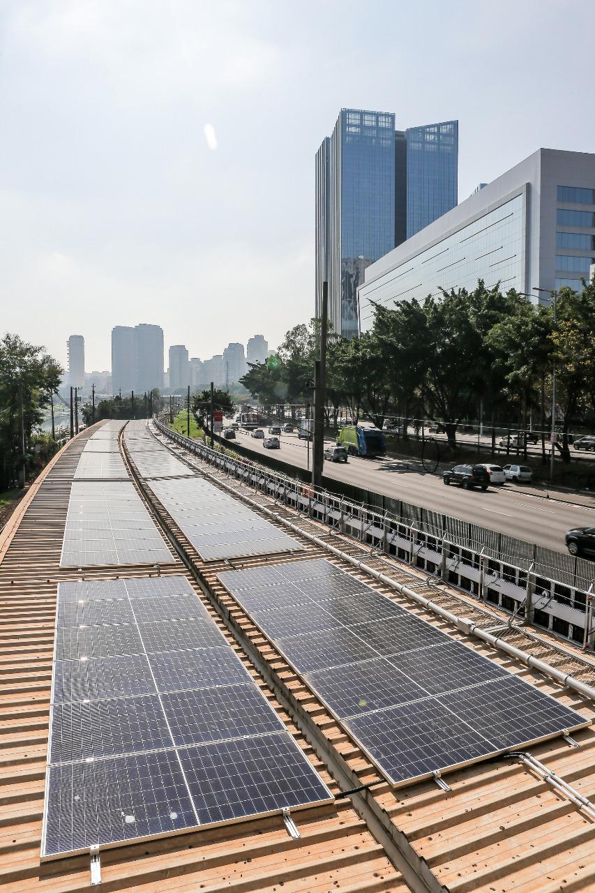 a imagem mostra placas fotovoltaicas acima do teto da estação vila olímpia, com a cidade no fundo