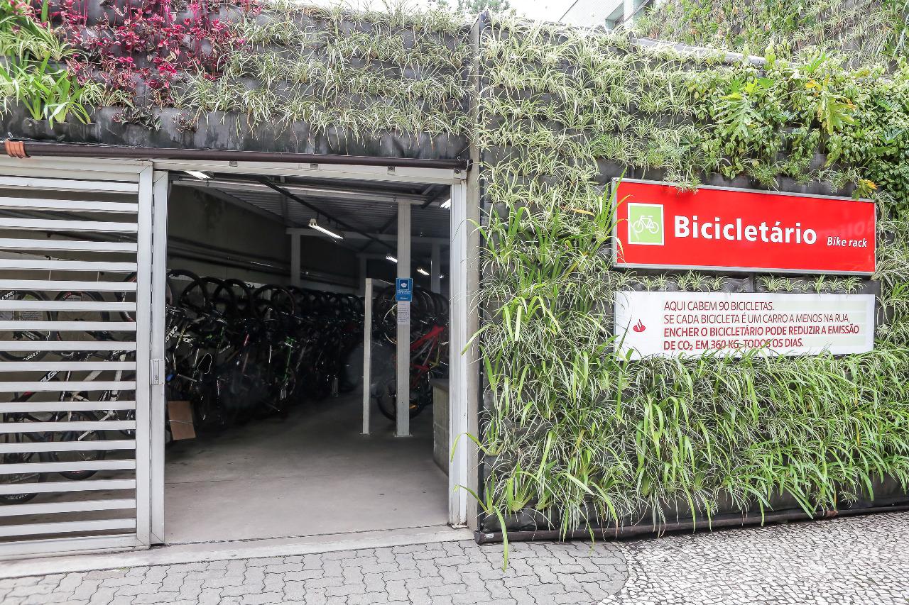 bicicletário inaugurado na estação vila olímpia da cptm, com placa identificando na direita, entrada à esquerda e plantas na fachada toda