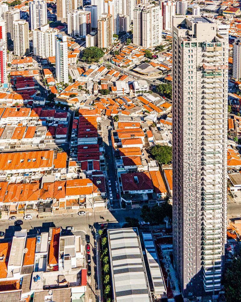A imagem, vista de cima, mostra o prédio da região do Tatuapé cobrindo diversas casas com sua sombra extensa.