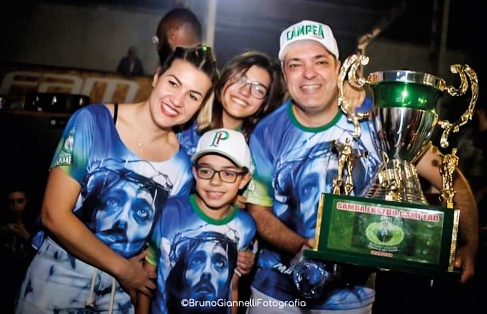 anna e marcelo posando para a foto com os filhos giovanna e guilherme, no carnaval em 2020. Todos estão com camisa da escola de samba Mancha Verde e marcelo está segurando o troféu de campeão do carnaval