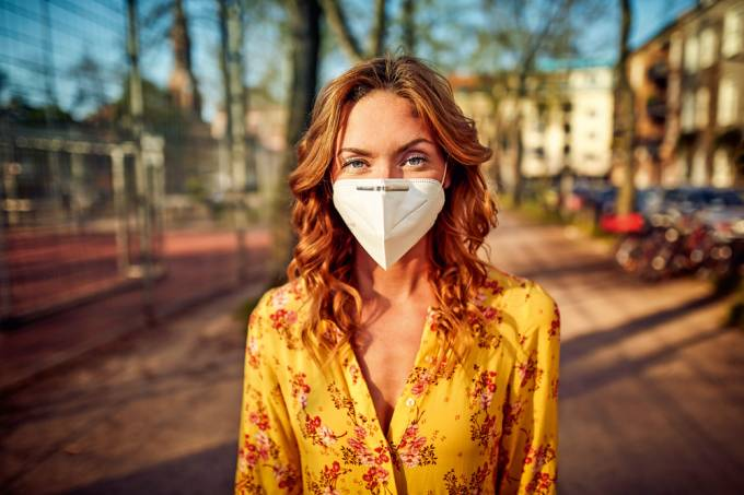 Red-haired woman wearing a FFP2 face mask in the city