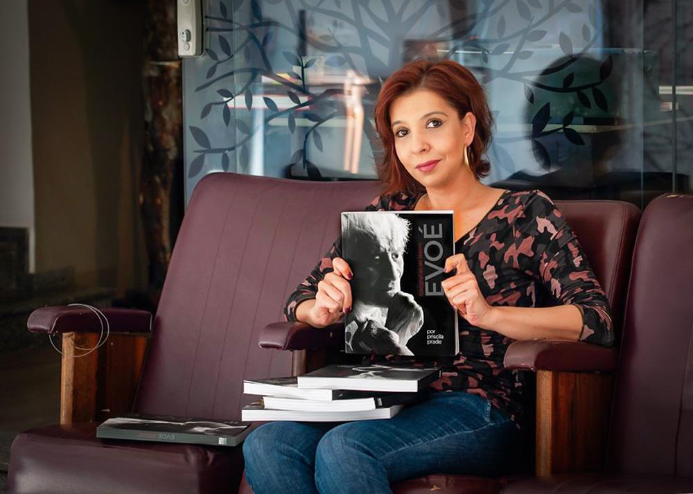 A autora Priscila Prade segura seu livro