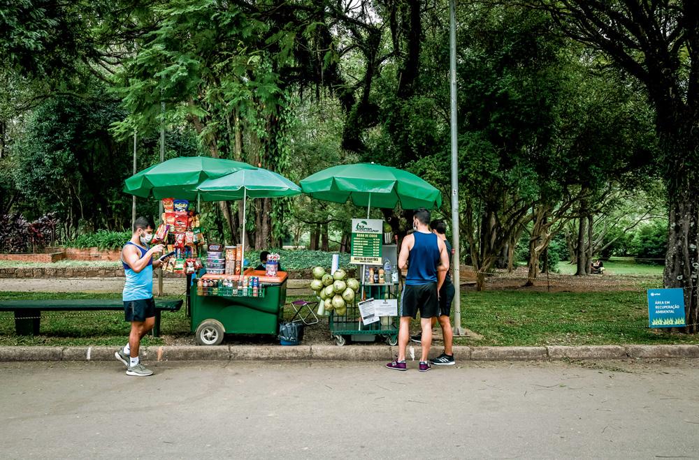 A imagem mostra um carrinho com guardo-sol e dois clientes olhando o que tem de opções nele dentro do Parque Ibirapuera