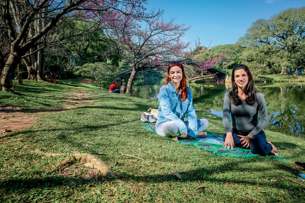 A imagem mostra as duas amigas sentada sobre a grama do Ibirapuera, sorrindo para a câmera.