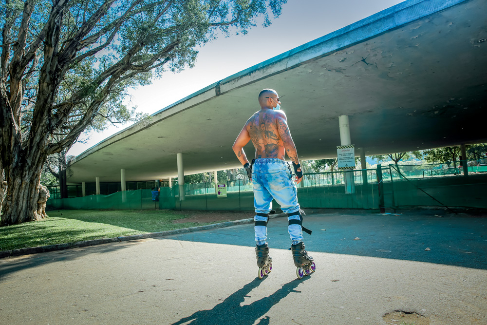 A imagem mostra Bruno, de patins, em frente a marquise fechada do Parque Ibirapuera