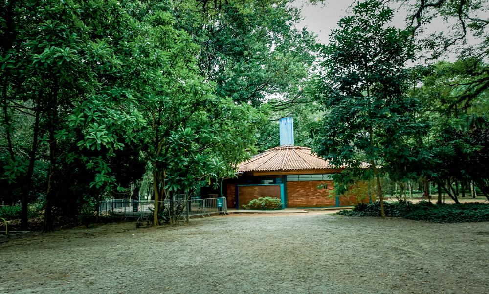 A imagem mostra uma pequena casa escondida entre árvores do parque