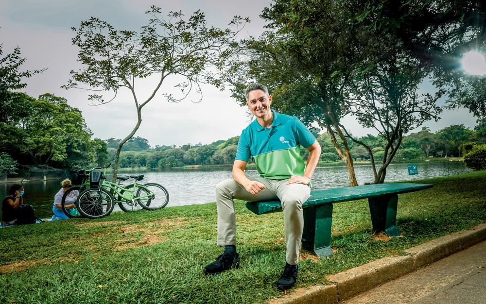 A imagem mostra Lloyd sentado em um banco no parque Ibirapuera. Ele sorri para a câmera com a mão no seu joelho.