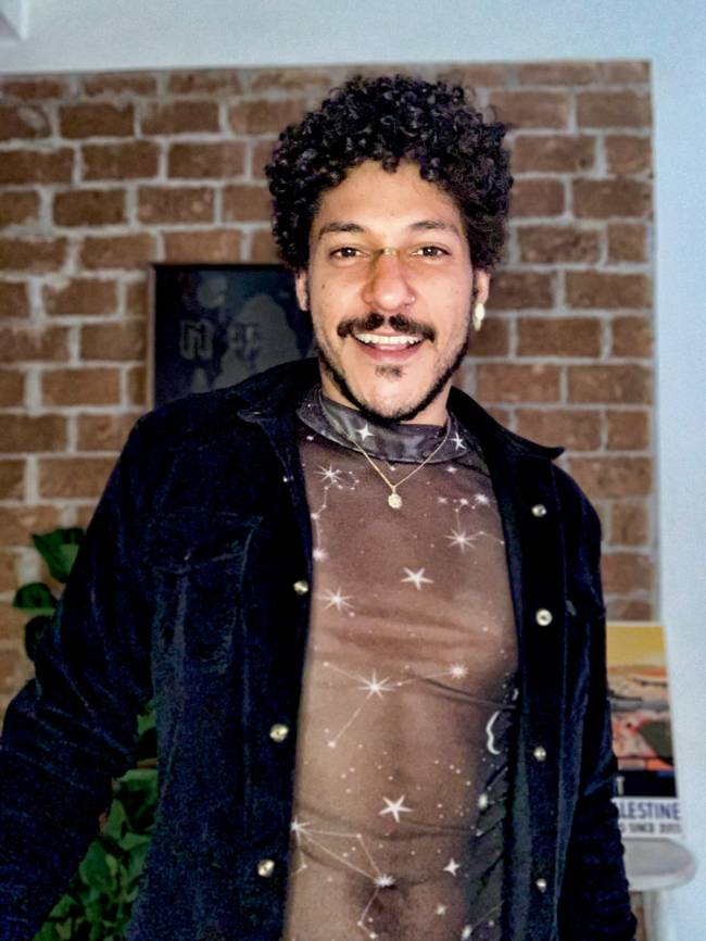 Homem negro com cabelos cacheados olha para a câmera sorrindo. Usa blusa transparente com estrelas