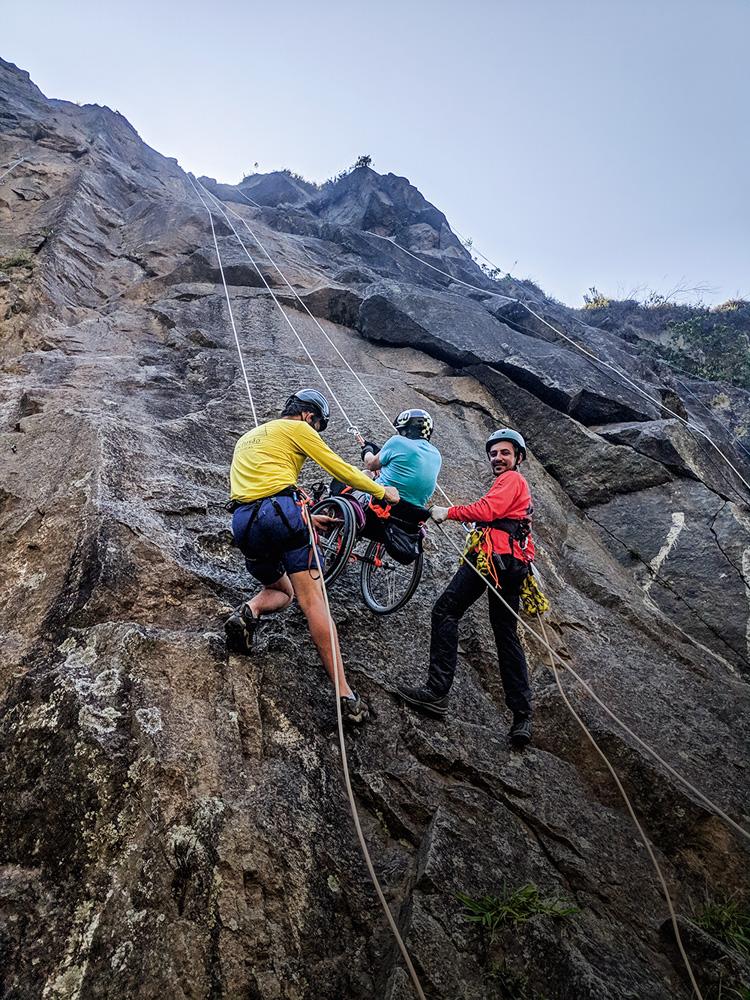 imagem de precipício da pedreira com pessoas o escalando, dois instrutores auxiliando um cadeirante