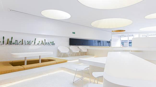 Segundo andar da cafeteria We Coffee na Liberdade, com paredes e móveis brancos.