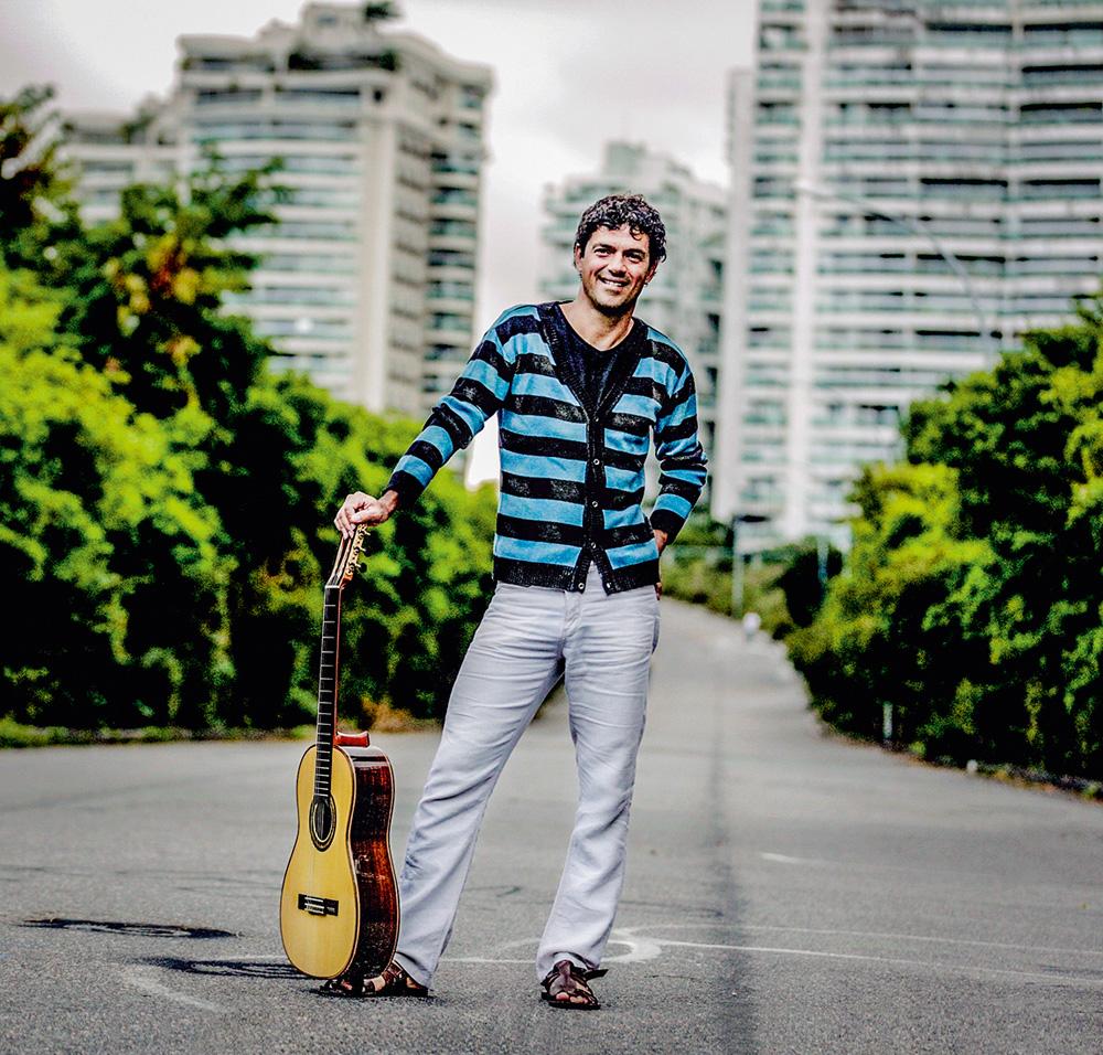 Um homem posa com um violão apoiado no chão ao seu lado. Ele está sorrindo em um cenário com prédios e árvores