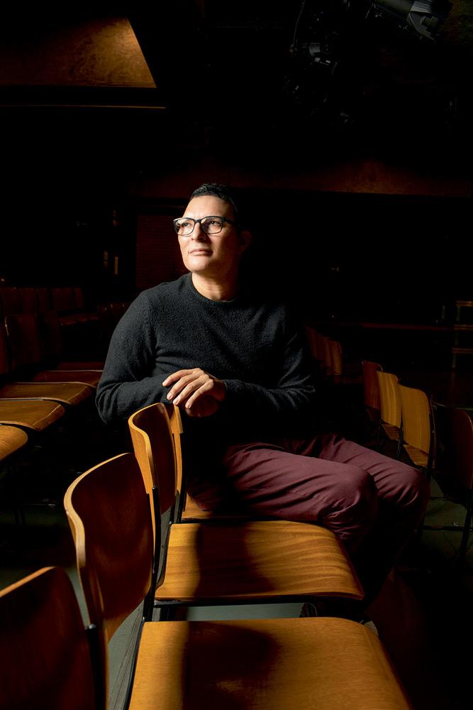 leandro lehart sentado em cadeira de auditório da ccsp com o busto arqueado horizontalmente olhando para cima