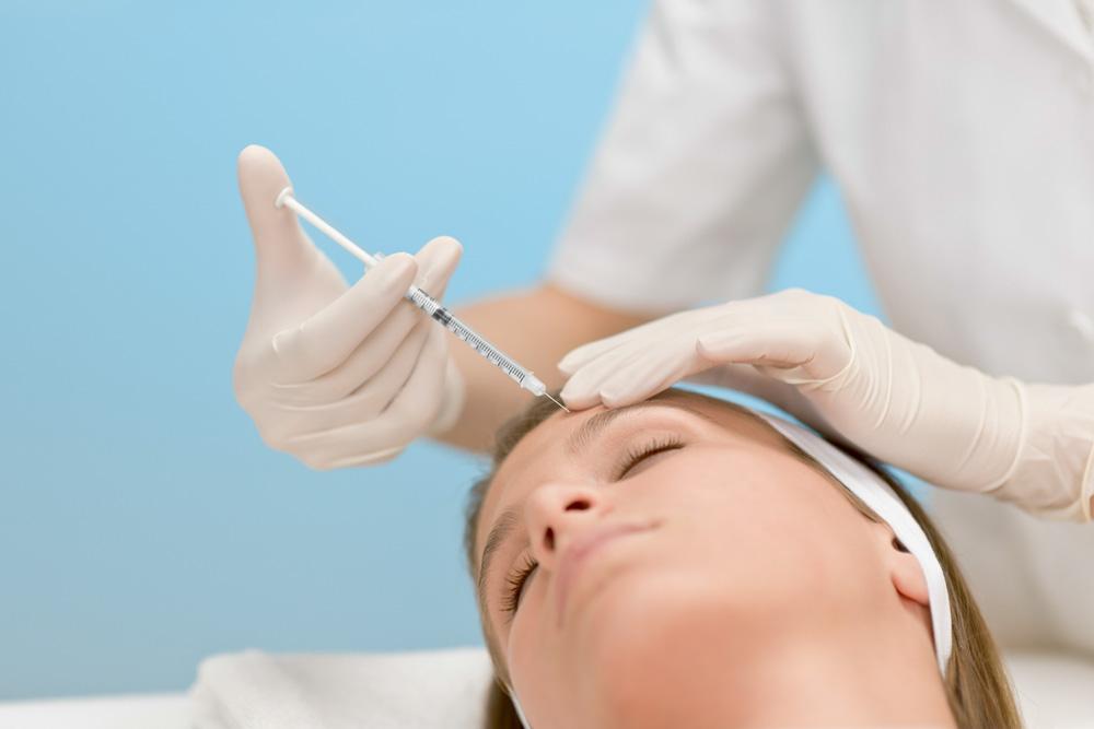 pessoa deitada levando injeção de botox na testa