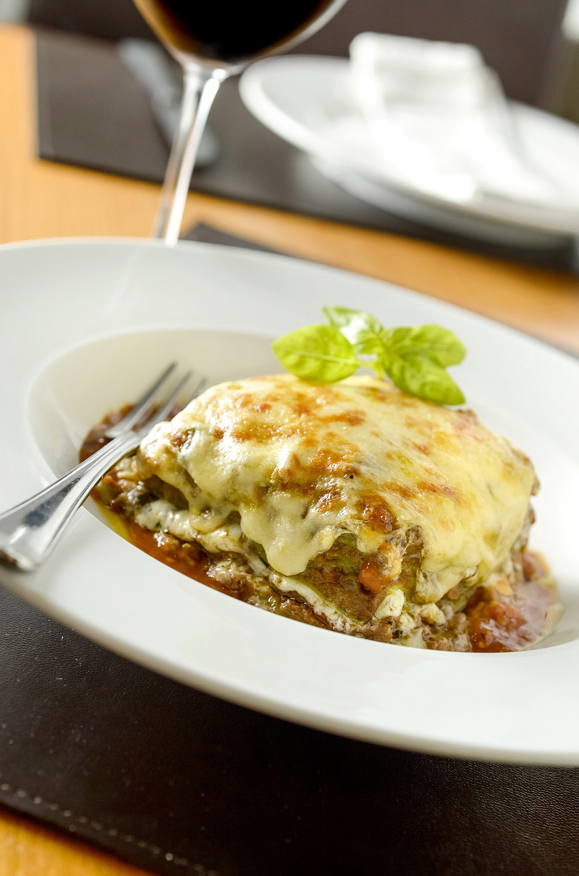 Pedaço quadrado de lasanha à bolonhesa coberta por queijo em prato fundo de louça branca com garfo apoiado do lado esquerdo. Ao fundo, uma taça de vinho embaçada.