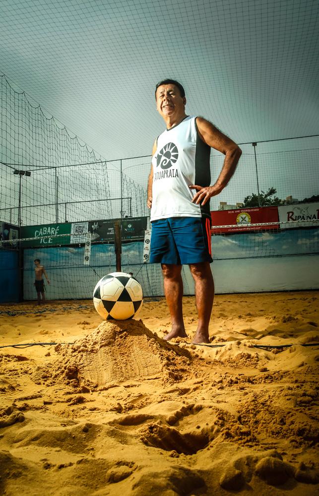 A imagem mostra Torralbo em uma quadra de futevôlei, com a bola posicionada em sua frente sobre um montinho de areia.
