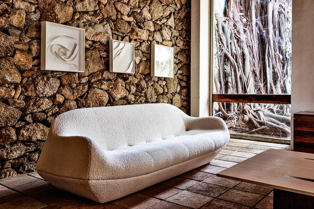 Um sofá branco em uma sala. Há quadros na parede e um pedaço de mesa de centro, que foi cortado pela foto