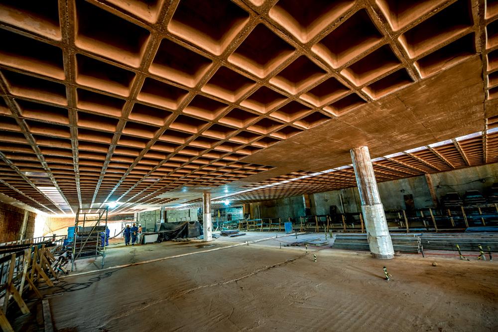 A imagem mostra um andar vazio do Museu do Ipiranga. No teto, é possível ver o formato de grelha, sendo ele inteiro quadriculado com buracos quadrados.