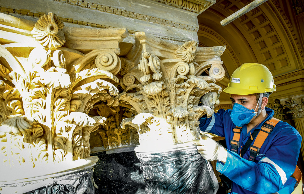 A imagem mostra Antonio, equipado com capacete e máscara, retocando uma estrutura com pincel.