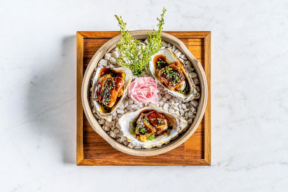 Foto tirada de cima de prato de cerâmica sobre sousplat de madeira em cima de bancada de mármore. No prato, com pedras e flor para decorar, aparecem três ostras com foie gras. Pedida do Makoto.