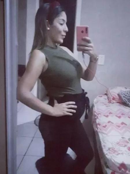 Foto de moça grávida posando de lado, em frente a um espelho.