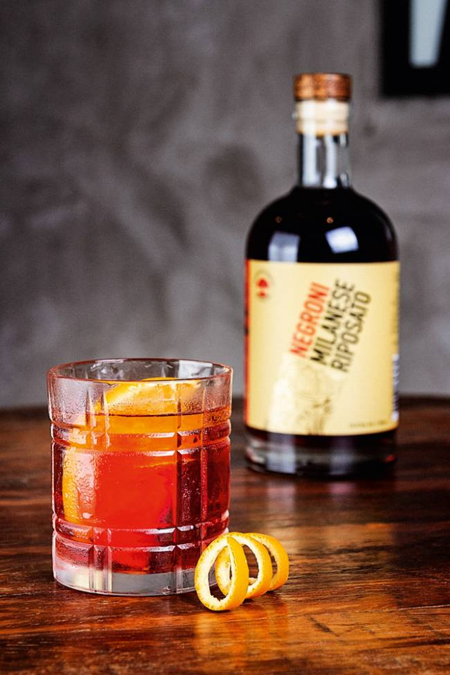 Sobre bancada de madeira, garrafa de Negroni ao fundo à direita e mais a frente um copo com a bebida servida mais fatia de laranja.