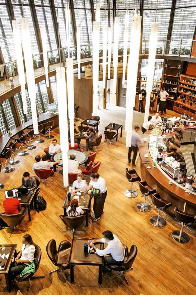 Foto tirada do mezanino do salão oval do extinto Octávio Café. À esquerda, fileira de mesas e, à direita, bancada com banquetas.