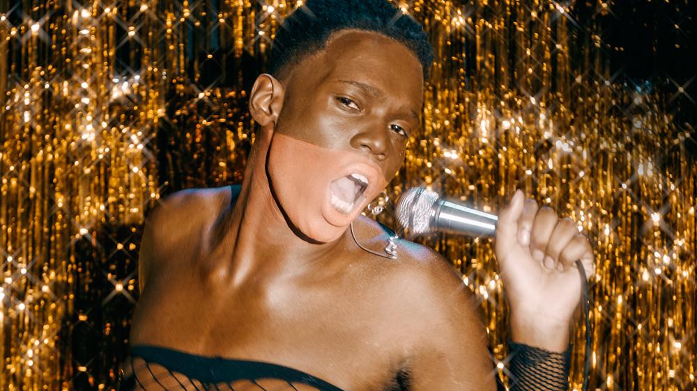 homem negro com detalhe no rosto cantando com uma cortina dourada brilhante no fundo