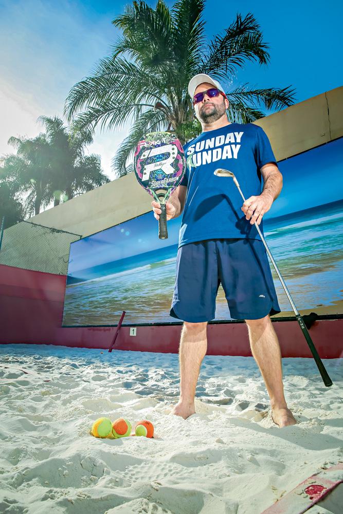 A imagem mostra Philippe, em uma quadra de beach tennis, com sua raquete e taco de golf. Ele está com óculos escuros e boné.