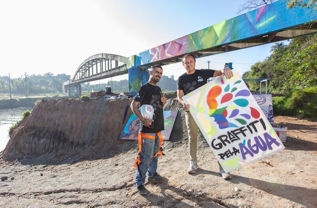 Gamão (esquerda) e Rodrigo Cordeiro, idealizadores do projeto Graffiti pela Água. Ambos posam em frente a ponte colorida. Rodrigo segura placa com título